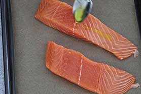a spoon with oil drizzling over the salmon.