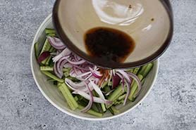 tossing pickling juice onto cucumber and onions