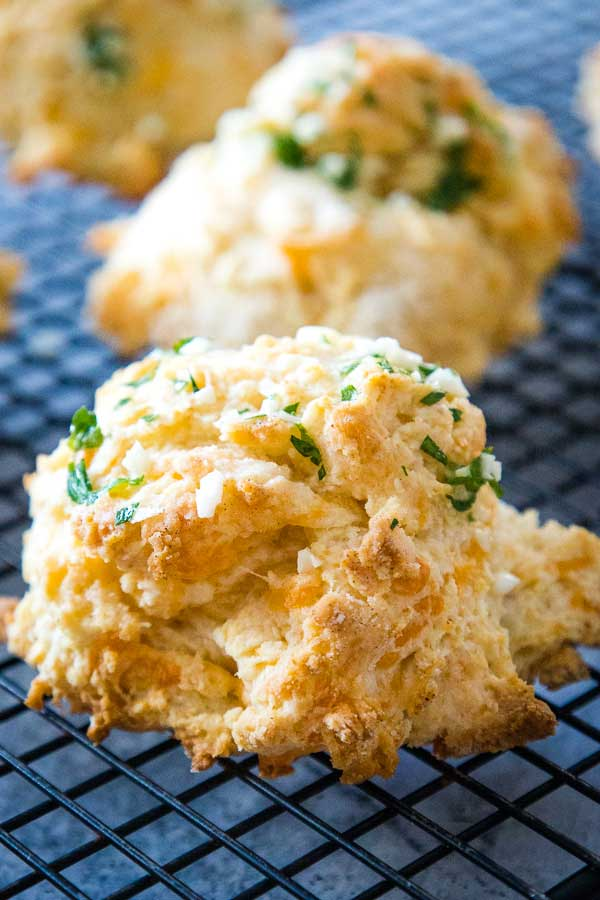 Golden baked garlic cheddar biscuits on a cooling rack with small pieces of garlic and fresh green parsley butter topping.