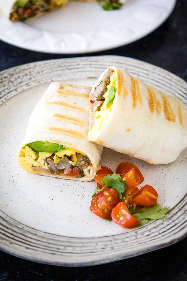 Angled overhead shot of a cut breakfast burrito on a plate with a side of cherry tomatoes and cilantro.