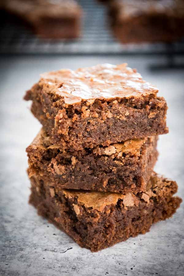 a stack of three brownies with more brownies in the background on a cooling rack.