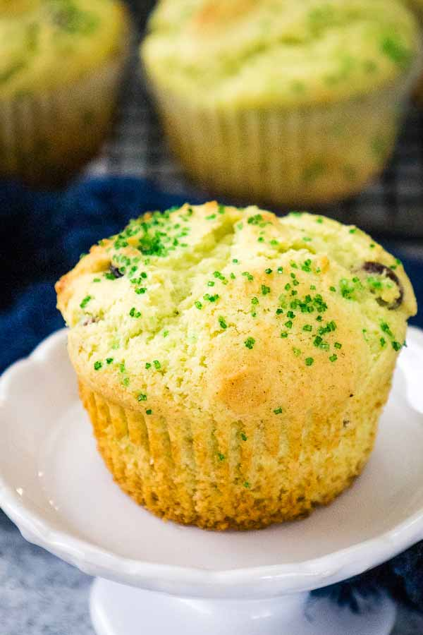 whole pistachio muffin on a white plate with muffins in the background.