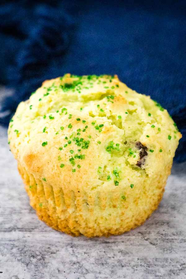 Pistachio Muffin with wrapper removed with a blue napkin in the background.