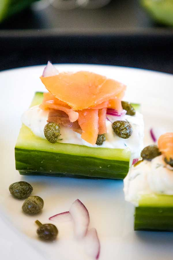 Stuffed Cucumber with Salmon, Red Onions, and Capers on a white plate.