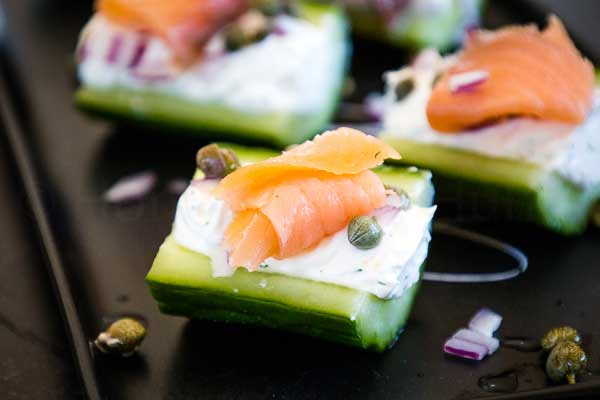 Up close visual of a stuffed cucumber with cream cheese filling topped with smoked salmon, red onions, and capers.