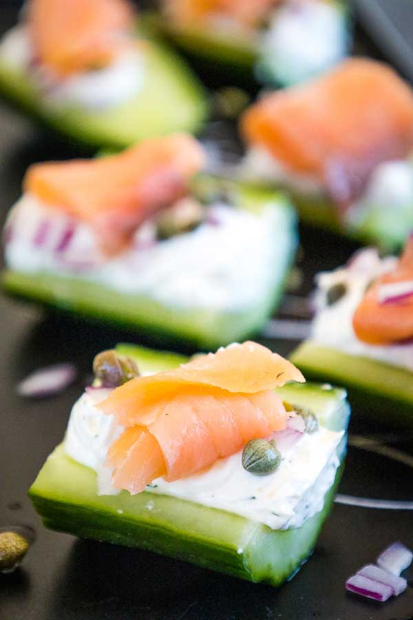Stuffed Cucumber Appetizers with Salmon, Red Onion, and Capers on a black serving tray