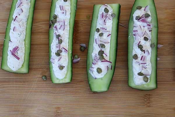 cucumber boats with cream cheese stuffing and sprinkled with onion and capers.