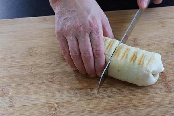 A hand holding the burrito while it is being cut in half with a knife on a wooden cutting board.
