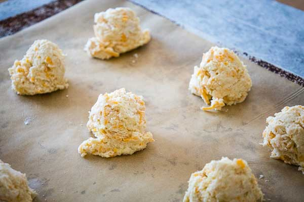 Raw biscuit dough dropped onto a brown parchment paper lined rimless cookie sheet.