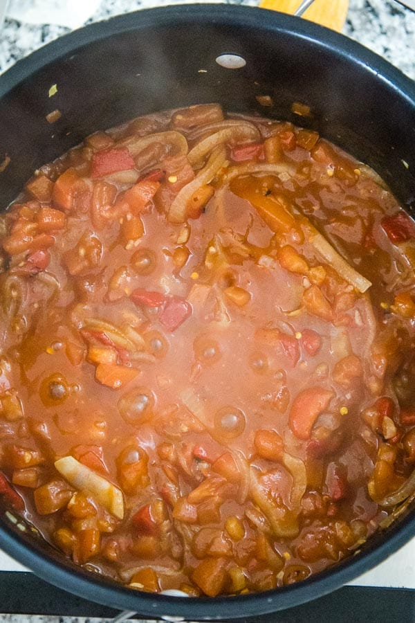 The Tomato Chutney Recipe in a dutch oven with all the ingredients combined and simmering with bubbles coming to the top of the chutney.