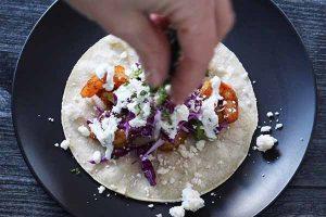 Sprinkling assembled shrimp taco with cilantro