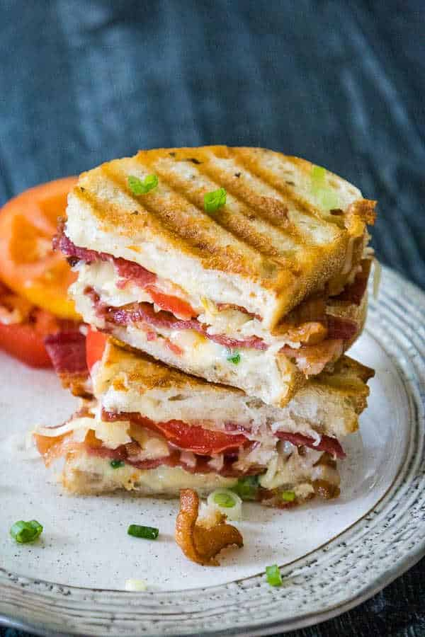 Bacon Tomato Grilled Cheese Sandwich with golden grilled marks cut in half and stacked showing the inside of the sandwich with the layers of bacon, tomato, and cheese sprinkled with green onion tops, with two heirloom tomato slices blurred in the background.