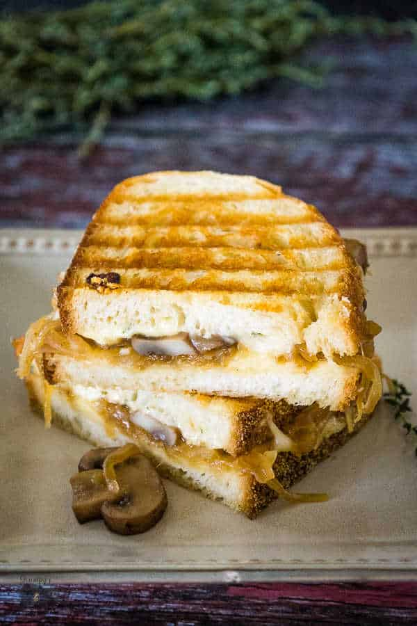 Grilled Cheese Sandwich with sauteed mushrooms in the sandwich and a mushroom on the plate next to the sandwich.
