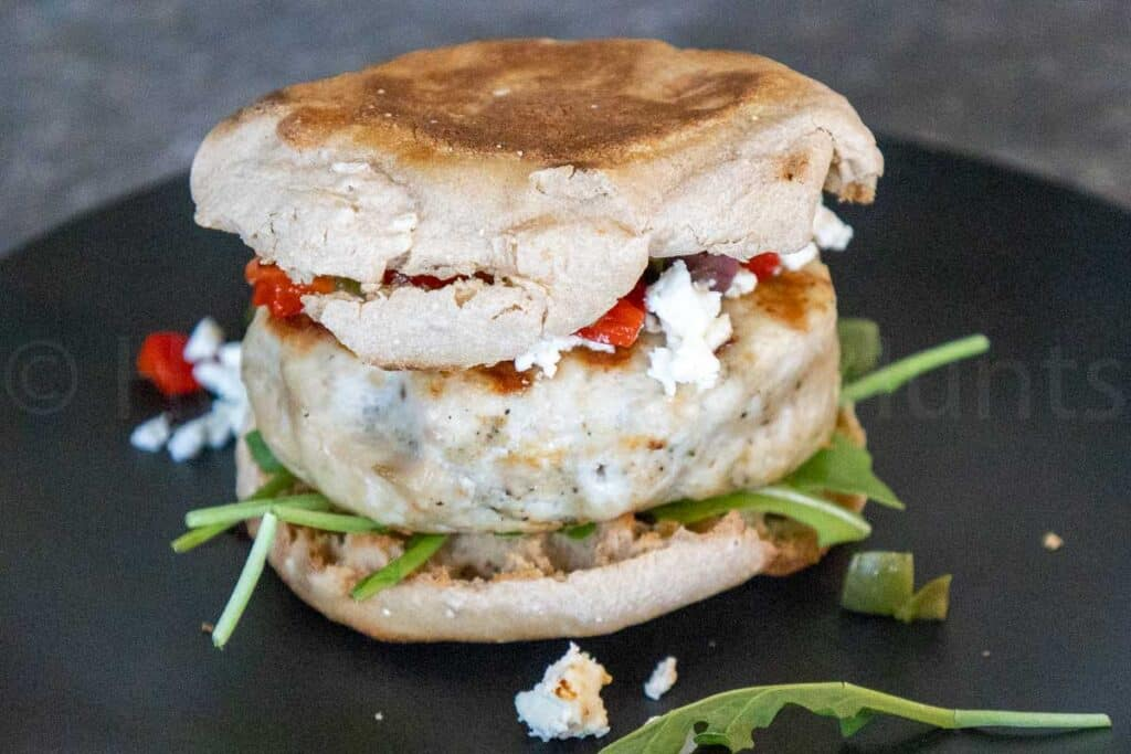 A Mediterranean Turkey Burger on a black plate sandwiched in an English muffin with feta cheese, roasted red peppers, and kalamata olive topping and arugula on the bottom half of the burger.