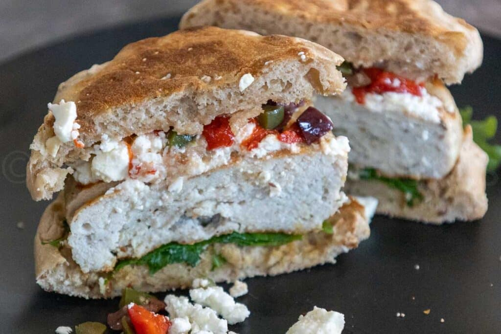 One fully assembled turkey burger cut in half showing the inside of the turkey burger with arugula on the bottom half of the bun, then the burger, topped with feta cheese, roasted red peppers, kalamata olives and the top half of the english muffin.