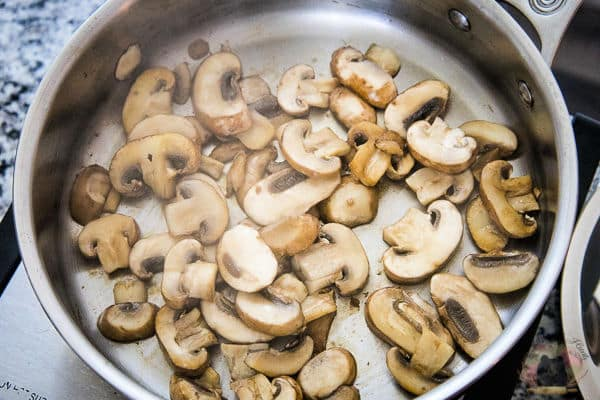 A stainless steel skillet on a hotplate with partially sauteed mushrooms inside of the skillet.