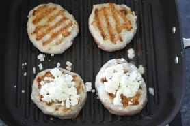 Four turkey burgers on a grill pan flipped over and showing grill marks on the top two burgers and feta cheese on the bottom two burgers.