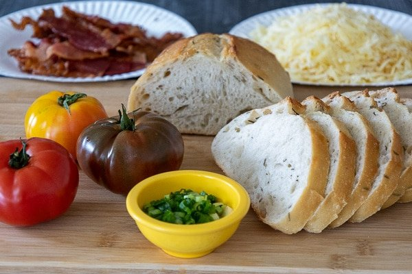 A red, yellow, and purple heirlooms tomato with a loaf of sliced , a yellow bowl of green onions and artisan bread and cooked bacon and grated cheese blurred in the background.