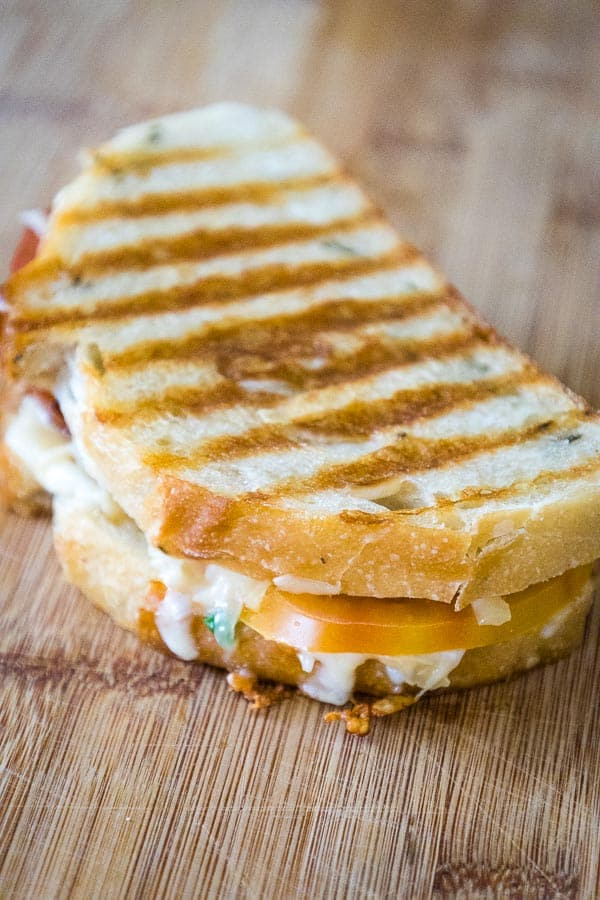 Grilled sandwich with golden grill marks and melted cheese coming out the sides with a yellow tomato peeking out the front edge and a red tomato at the back of edge.