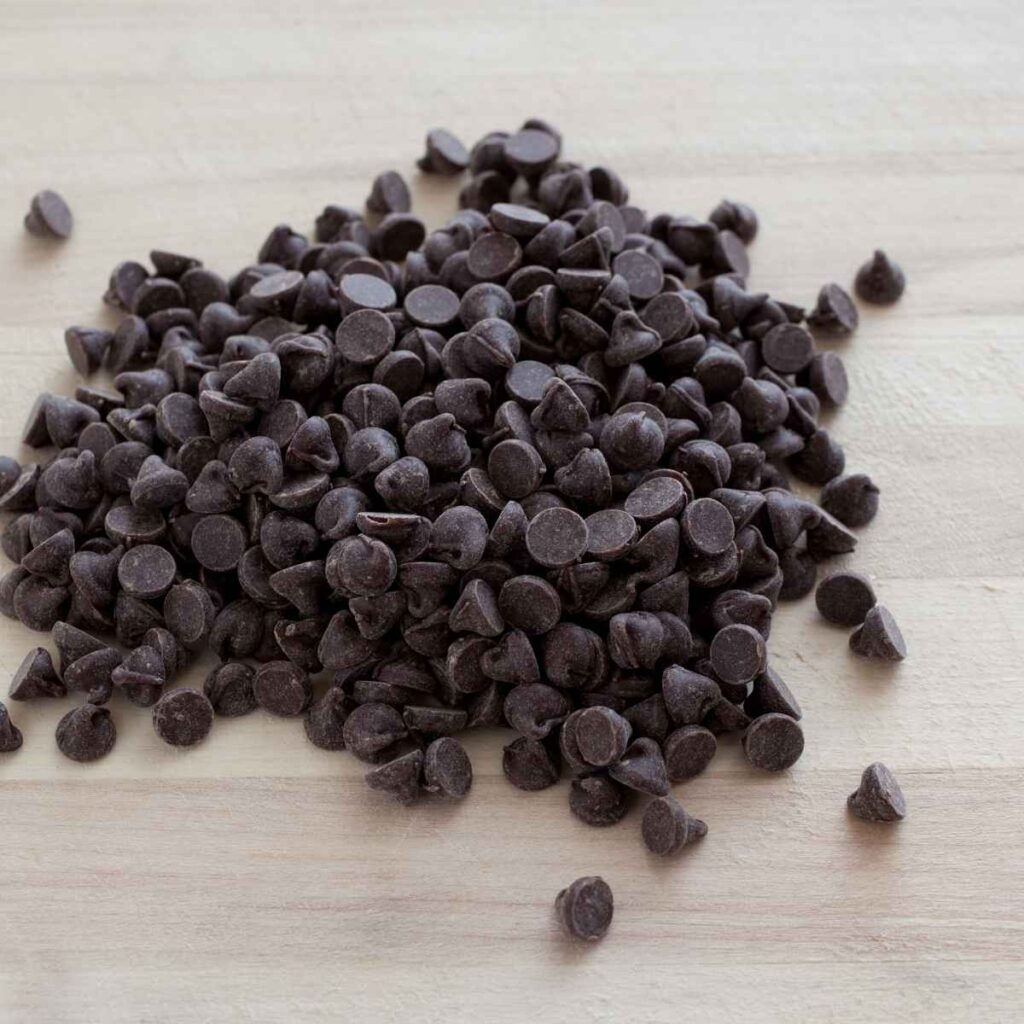 A pile of mini chocolate chips on a light wood cutting board.