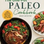 The cover page of The One-Pot Paleo Cookbook by Shelby Law Ruttan with an image of a black cast iron skillet holding a cooked bone in steak with green beans and grape tomatoes to the side of the steak.