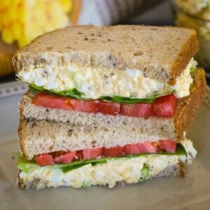 A sandwich made with egg salad, tomatoes, lettuce on wheat bread and cut in half and stacked with the two cut sides facing out.