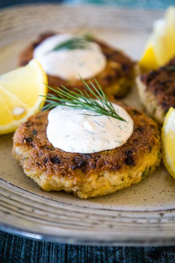 A plate of keto salmon patties topped with dill sauce, a sprig of fresh dill, and lemon slices arranged around the patties.