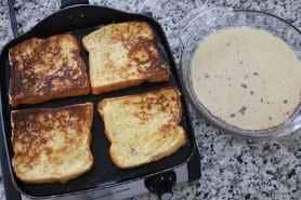 French toast on the griddle with the browned side up and batter to the right of the griddle.