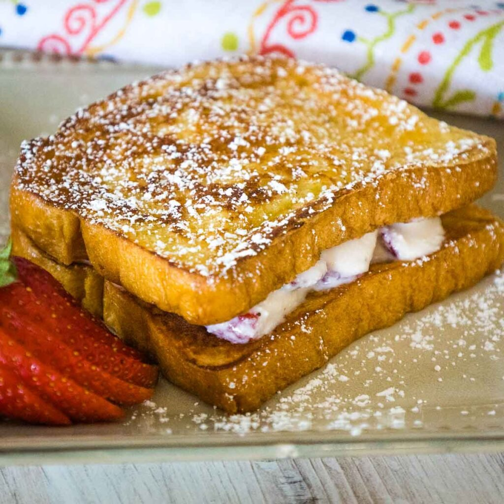 A cream colored plate with a serving of strawberry stuffed french toast with a strawberry on the left side of the french toast and a patterned pink green, yellow, blue and white napkin blurred in the backrground.