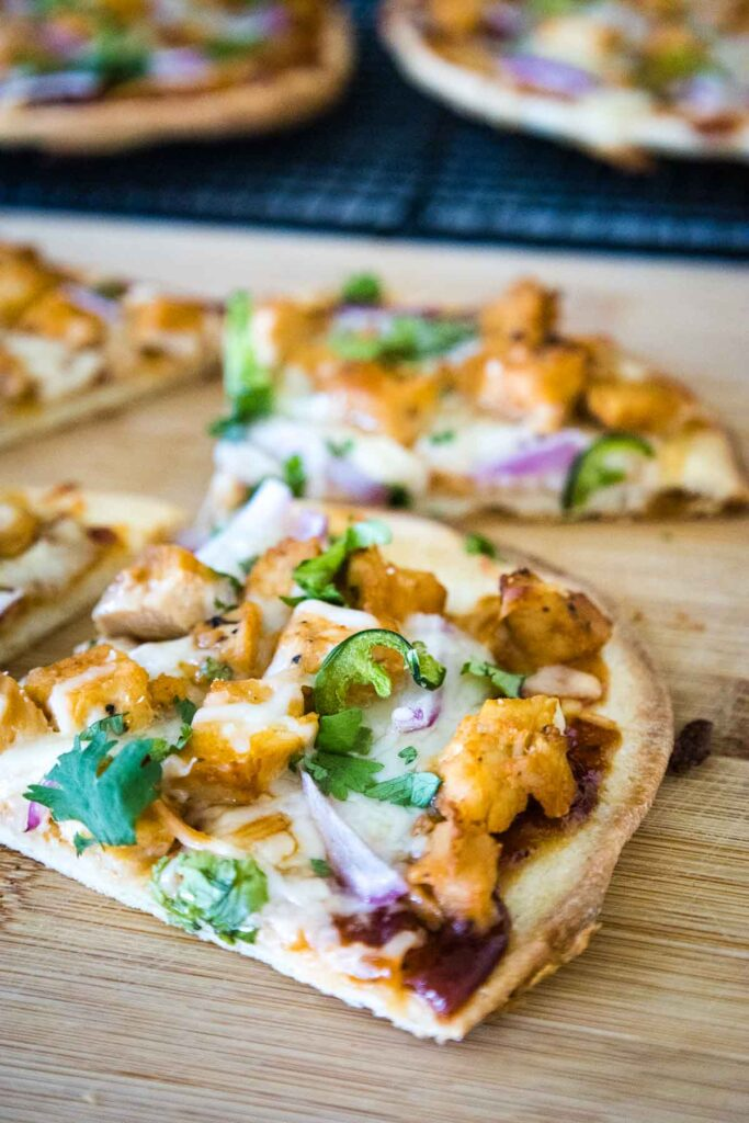 BBQ Chicken Naan Pizza topped with cheese, bbq sauce, chicken, red onion, jalapeno, and chopped fresh cilantro cut into triangle shaped slices sitting on a wooden cutting board