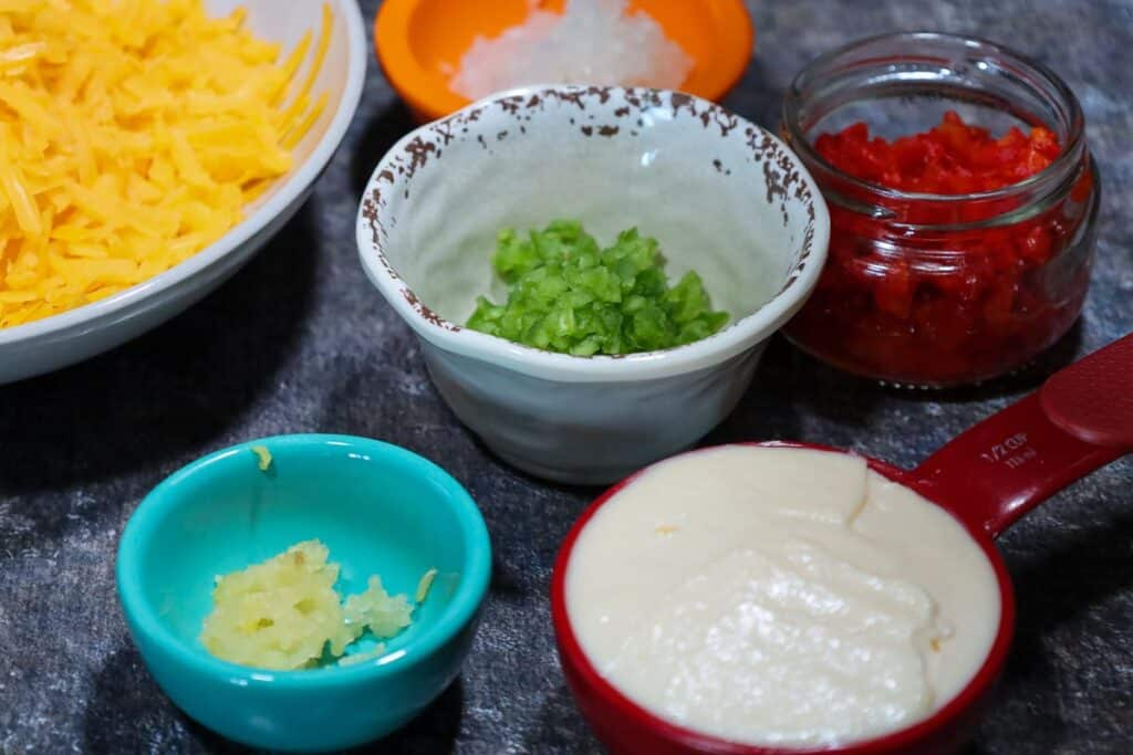 Ingredients for Jalapeno Pimento Cheese in prep bowls before mixing them together, starting from 12:00 and working clockwise: orange prep bowl with minced white onion, jar of drained pimentos, red measuring cup with mayonnaise, teal prep bowl with minced garlic, white bowl with shredded yellow cheddar and in the center a cream prep bowl with the minced jalapeno.