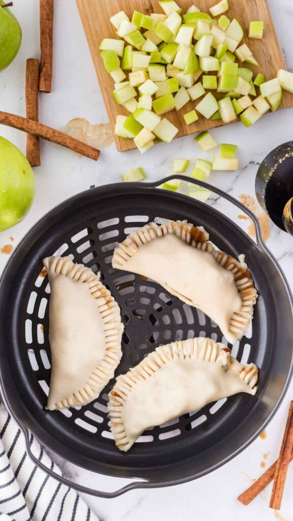 Three unbaked hand pies in the air fryer basket.