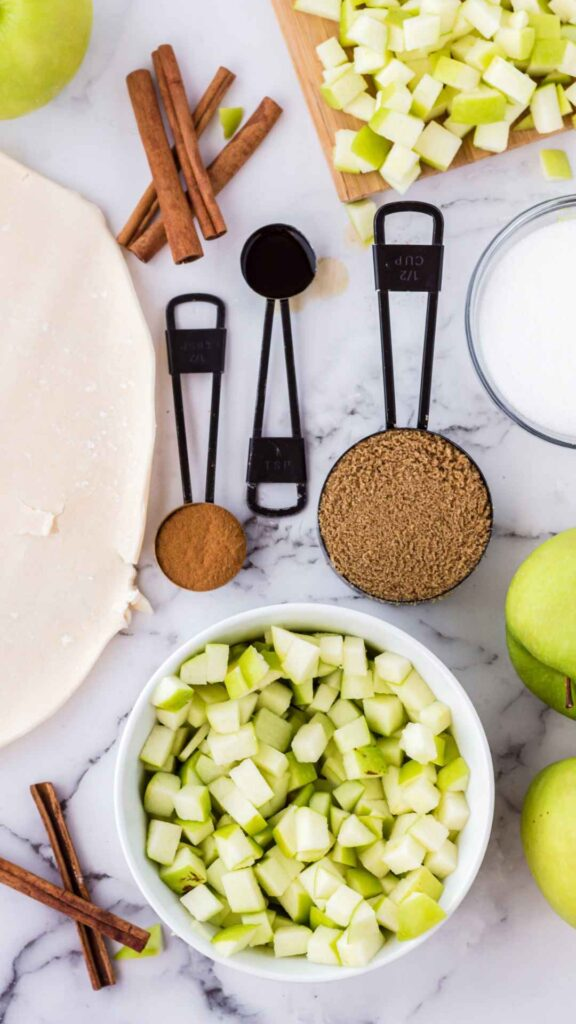 Overhead view of ingredients from left to right, top to bottom: four cinnamon sticks stacked on top of each other, diced granny smith apples with the skin on, a bowl of white sugar, a bowl of diced granny smith apples with the skin on, a section of pastry dough with cinnamon, vanilla extract, and brown sugar in the center.