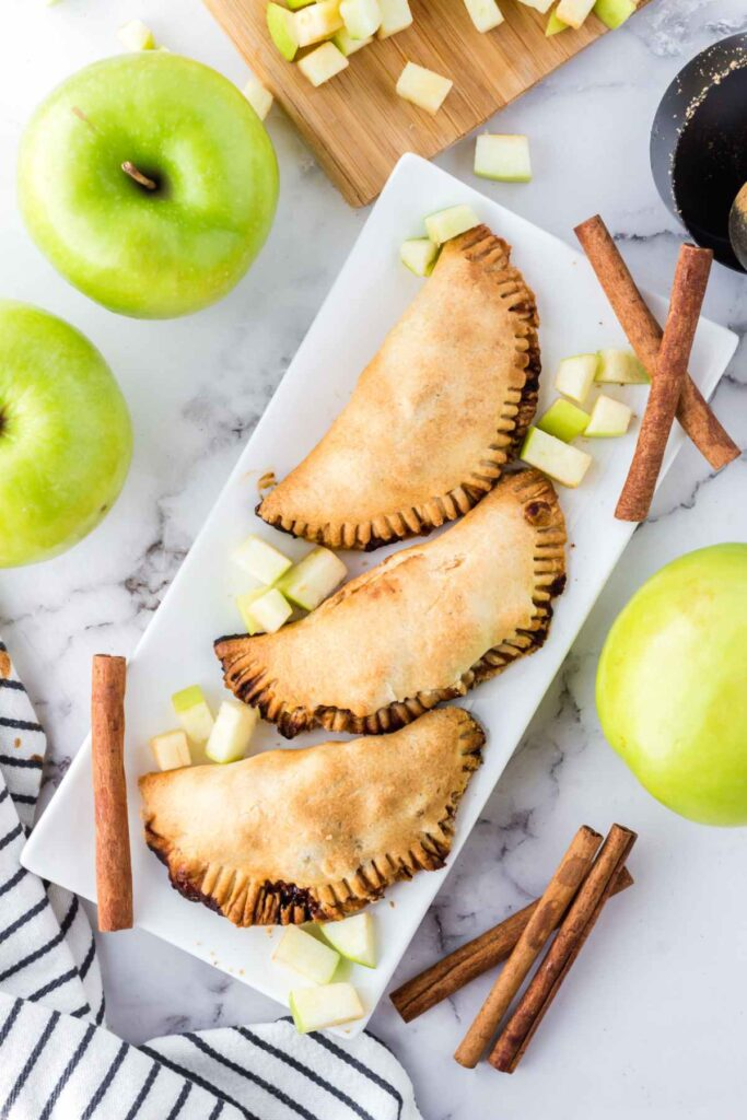 Overhead image of 3 apple hand pies on a white serving tray with diced granny smith apples sprinkled around the pies and cinnamon sticks scattered around the plate.