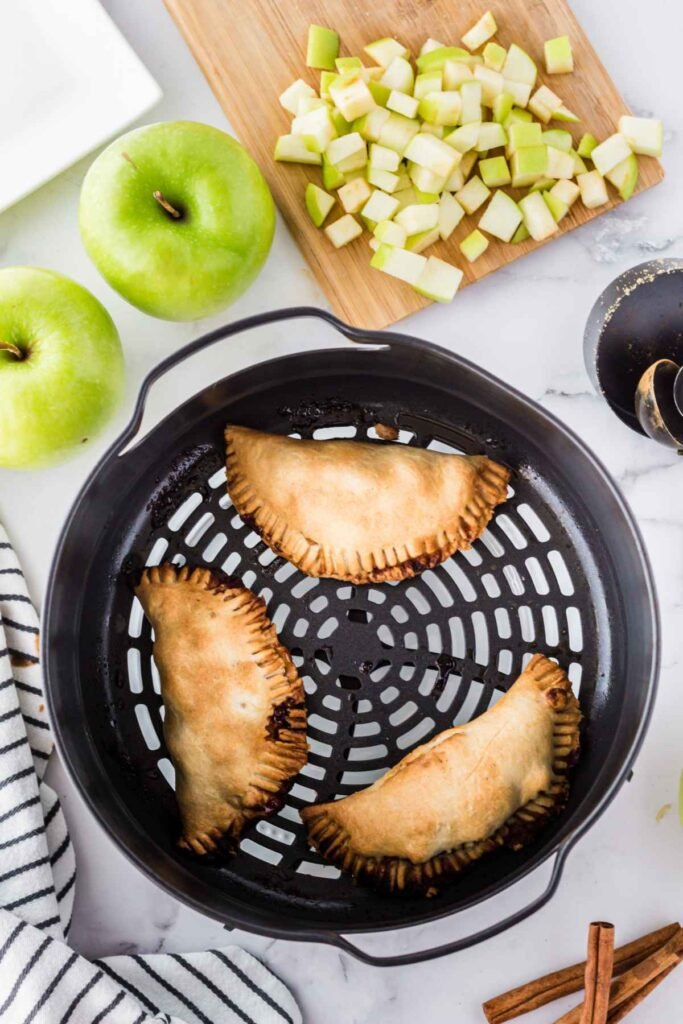 Three golden brown baked hand pies in the air fryer basket with two green granny smith apples to the top left, and diced granny smith apples on a cutting board to the top right of the image.