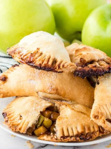 A pile of apple hand pies on a white plate with one pie broken in half to see the apple filling inside and 3 green apples blurred in the background.
