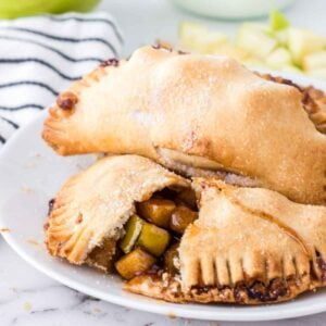 A pile of apple hand pies on a white plate with one pie broken in half to see the apple filling inside and chopped green apples blurred to the right in the in the background and a blue and white hand towel blurred to the left in the background.
