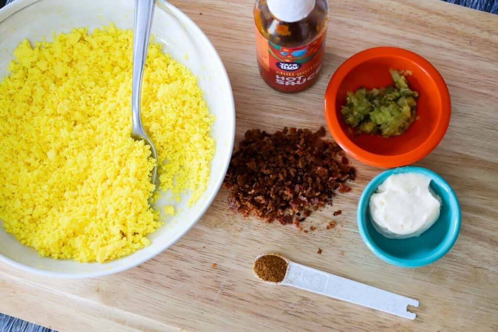 From left to right, a cream bowl with yellow mashed egg yolks, a bottle of chili garlic sauce, an orange prep bowl with pickle relish, teal prep bowl with mayonnaise, a white measuring spoon with cajun seasoning, and a pile of chopped bacon in the center.