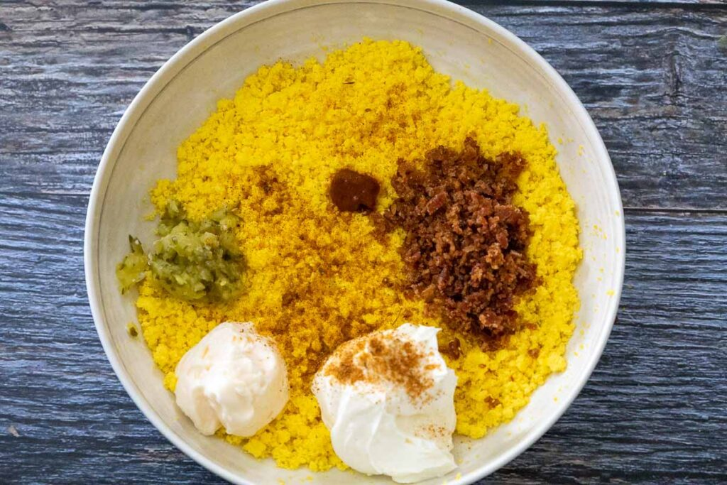A cream bowl with the mashed egg yolks and the remaining ingredients on top of the yolk, from top going clockwise, chili garlic sauce, chopped bacon, cream cheese, mayonnaise, and sweet pickle relish.