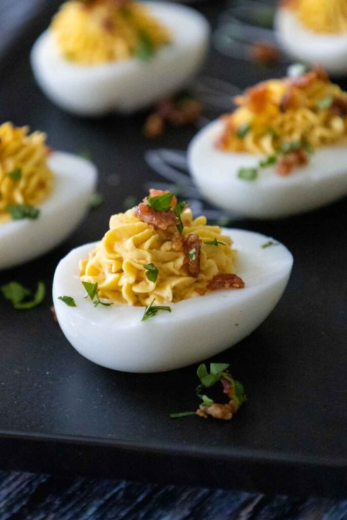 Cajun Deviled Eggs on a black serving tray with one egg prominent in the photo and 3 other eggs blurred in the background.