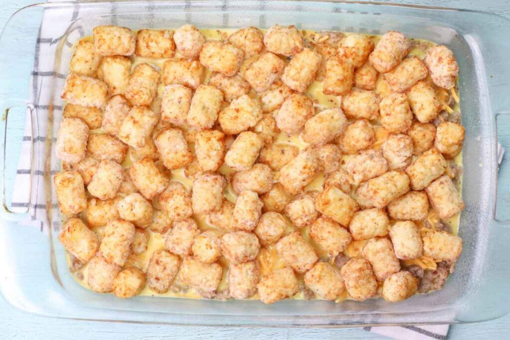 Clear glass dish with the frozen tater tots on top of the casserole ingredients before baking.