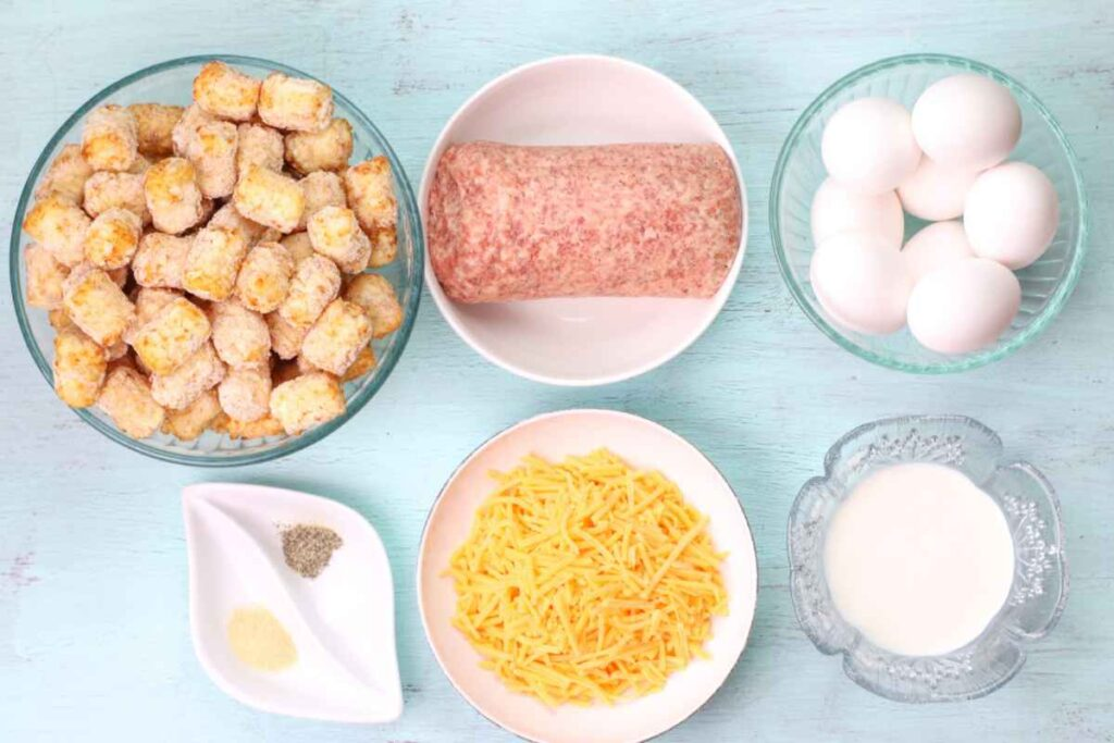 A line up of ingredients from top left, A bowl of tater tots, ground pork sausage in a white bowl, a glass bowl with eggs, below the tater tots is a bowl with salt and pepper, a white bowl with shredded yellow cheese, and a clear glass bowl with half and half.