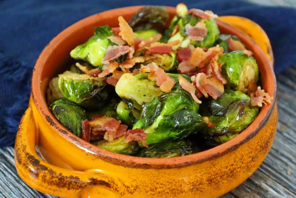 Air Fryer Brussels Sprouts with Browned Balsamic Butter topped with crispy bacon in an orange bowl.