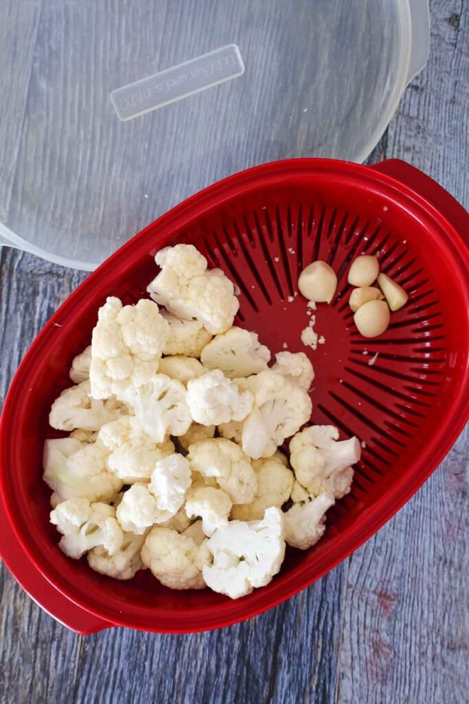 Raw cauliflower and garlic in a red microwavable steamer with the lid in the background.