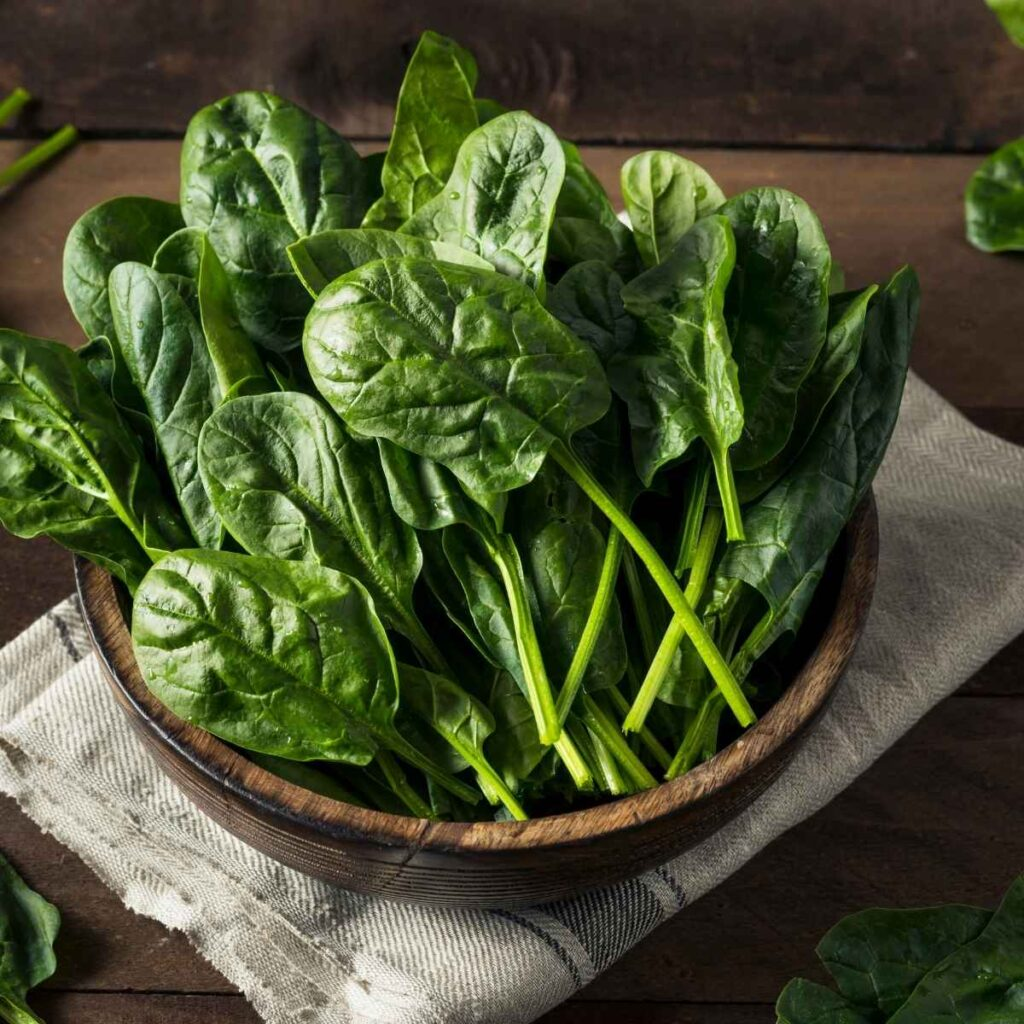 A dark brown wooden bowl full of fresh spinach leaves sitting on top of a cream colored rustic cloth.