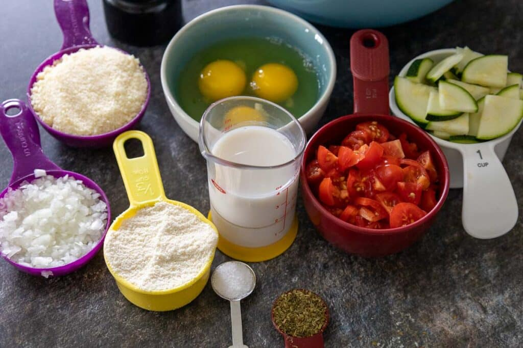 Ingredients starting at 12:00 and going clockwise, 3 eggs in a bowl, a white measuring cup with sliced zucchini, a read measuring cup with chopped tomatoes, a clear measuring cup with almond milk, a teaspoon of italian seasoning, ½ teaspoon of salt, a yellow measuring cup with coconut flour, a purple measuring cup with finely diced white onion, and a purple measuring cup with grated parmesan cheese.