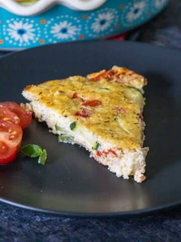 One slice of Impossible Zucchini Pie on a black plate with a halved tomato on the left side and a blue and white flowered pie dish blurred in the background.