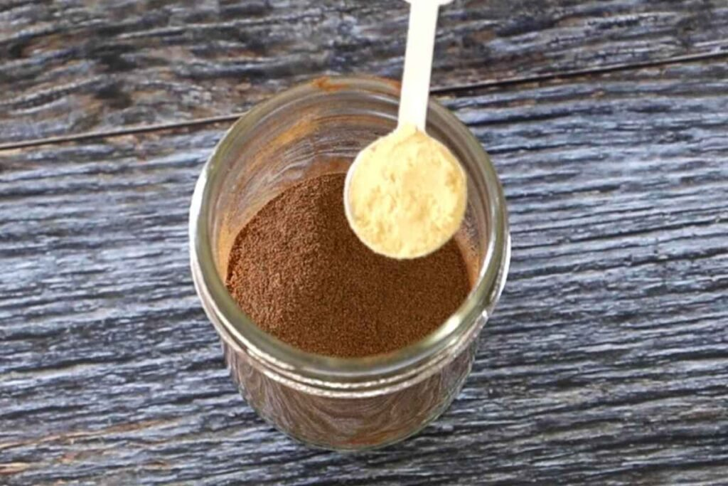 A teaspoon over top of the spice jar filled with ground ginger.