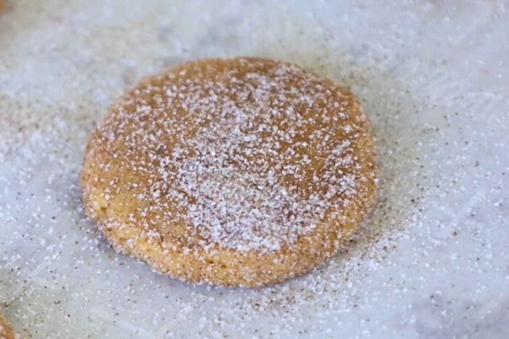 Upclose image of one sugar coated cookie dough ball that has been flattened out on parchment paper.