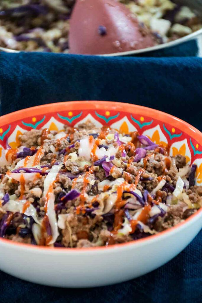 Eggroll in a Bowl made with ground venison, green and red cabbage, and drizzled with sriracha sauce with a skillet blurred in the background.